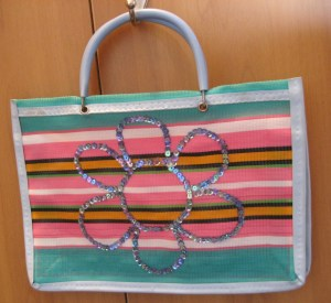A simples sacolinha de feira fica mais alegre com o bordado de lantejoulas. Usei fio de nylon e desenhei a flor com giz de costura à mão livre.